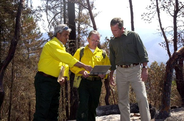 President George Bush visiting the site of the Squire Peak forest fire, Ruch, Oregon, for surveys of the damage, discussions with Bureau of Land Management, state, and local officials and firefighters, and policy announcements. Photograph was selected for use in Department of Interior video on the tenure of Secretary Gale Norton