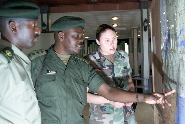 Republic of Rwandan Army Major (MAJ) Rugazora Emanuel (left), and US Army (USA) Captain (CPT) Michelle Snyder (right), Army Intelligence Officer, observe as Republic of Uganda Army Captain (CPT) Karugaba Godwin (center) Ugandan Logistics Officer, uses a map to point out possible routes from Entebbe, to a forward operating location during Exercise MEDFLAG 02-1. MEDFLAG is a US European Command multinational multi-service medical exercise designed to provide care, training and disaster management for Doctors, Nurses, and Technicians in different countries around the world