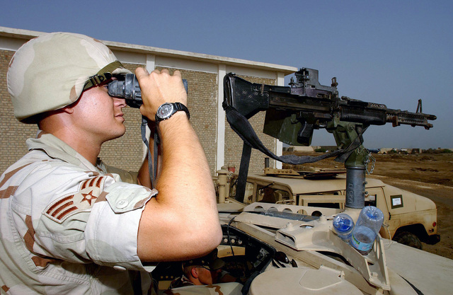 A US Air Force (USAF) Security Police (SP) assigned to the 438th Expeditionary Security Forces Squadron (ESFS), uses a pair of binoculars to scan the perimeter for atop a M998 High-Mobility Multipurpose Wheeled Vehicle (HMMWV) armed with a 7.62mm M60 general purpose machine gun while providing security for a forward deployed location supporting Operation ENDURING FREEDOM