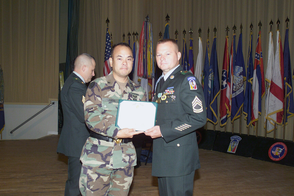 Brigadier General (BGEN) Jason K. Kamiya, Commander of the Joint Readiness Training Center and Fort Polk, presents Sergeant First Class (SFC) Scott Haymaker, B CO, 1/509th Infantry Battalion, with a certificate during his induction into the Sergeant Audie Murphy Club at Fort Polk, Louisiana