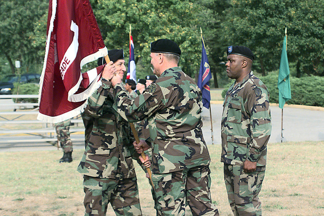 Colonel (COL) Lairie O. Stabler (center), USA, outgoing commander, passes the Medical Department Activity (MEDDAC) flag to COL Jonathan Jaffin, Commander Walter Reed Health Care during the change of command ceremony. MASTER Sergeant (MSG) Jackie A. Horton (right), USA, SENIOR Medical NCO of the MEDDAC stands by as the guidon bearer