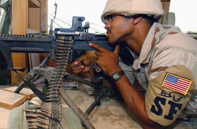 US Air Force (USAF) AIRMAN First Class (A1C) Sherife Davis, Security Forces Journeyman, 438th Expeditionary Security Forces Squadron (ESFS), mans his 7.62mm M60 general purpose machine gun as he watches over the front gate from a defensive fighting position (DFP) while providing security for a forward deployed location supporting Operation ENDURING FREEDOM