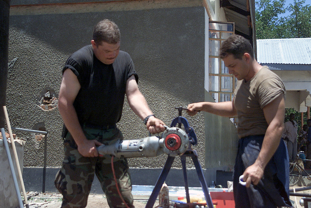 US Air Force (USAF) STAFF Sergeant (SSGT) Kevin Crumley and SSGT Kevin Avalon, plumbers from the 100th Civil Engineering Squadron (CES), Mildenhall, England fit a pipe for a new sink being built in the Aserat Clinic in support of MEDFLAG 2002
