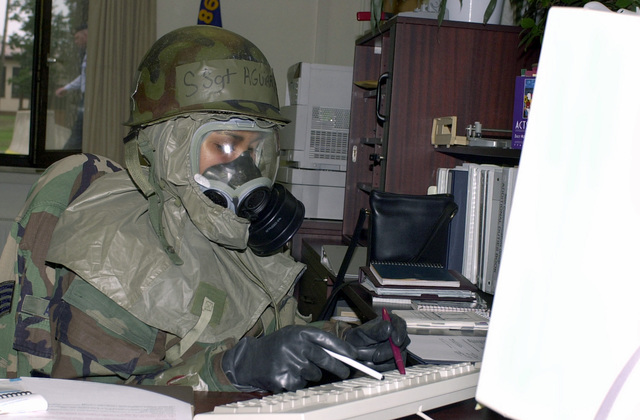 US Air Force (USAF) STAFF Sergeant (SSGT) Denise Aguiar, 86th Communication Group, Ramstein Air Base (AB), Germany, types correspondence during Warrior Day, while wearing her Mission-Oriented Protective Postures level 4 (MOPP-4) gear