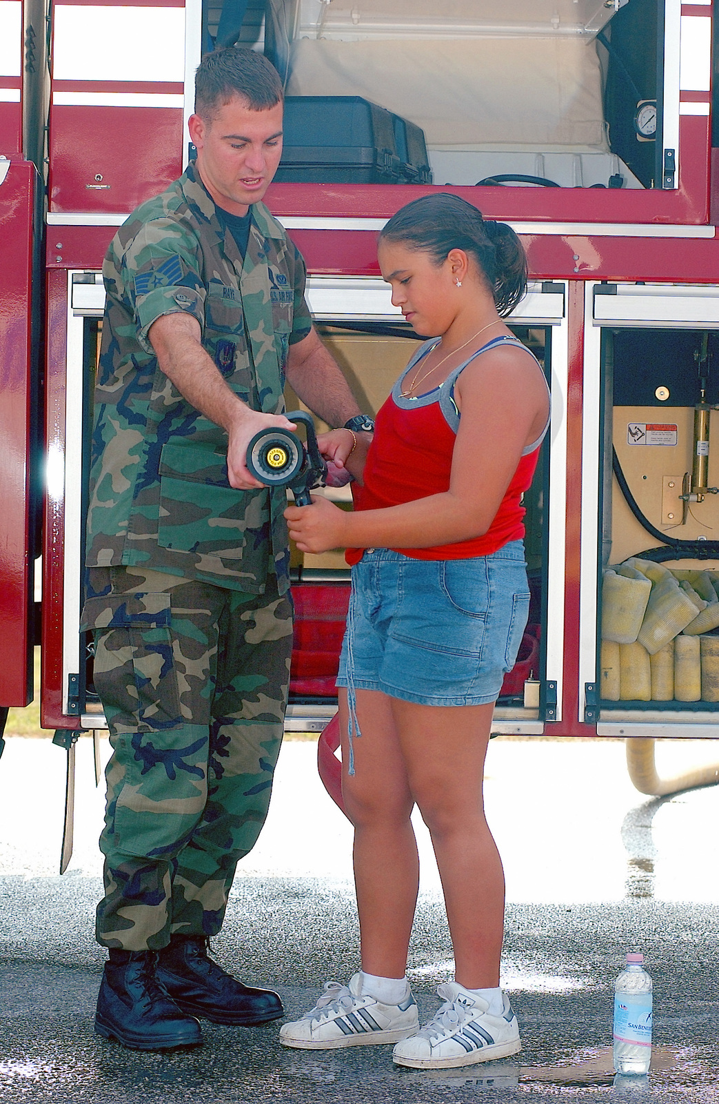 US Air Force (USAF) STAFF Sergeant (SSGT) Brayan Raye, a Fire Fighter, shows a child the hand lines off of the crash 8 T3000 fire truck during a tour of Aviano Air Base (AB) on Labor Day weekend
