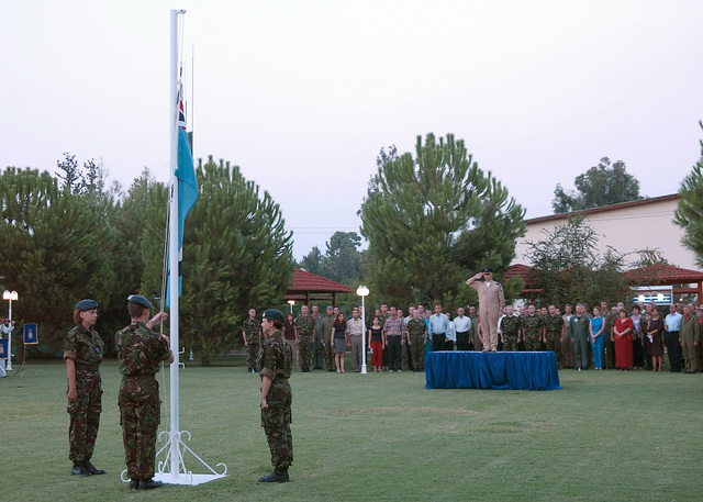 Royal Air Force (RAF), Group Captain (CPT) Osborne renders a salute to the ensign as Corporal (CPL) Helen Penny, CPL Ian Barrie and SENIOR Aircraft Woman Marie Ponton act as Honor Guard at the Battle of Britain Observance held at Incirlik Air Base (AB), Turkey, during Operation NORTHERN WATCH