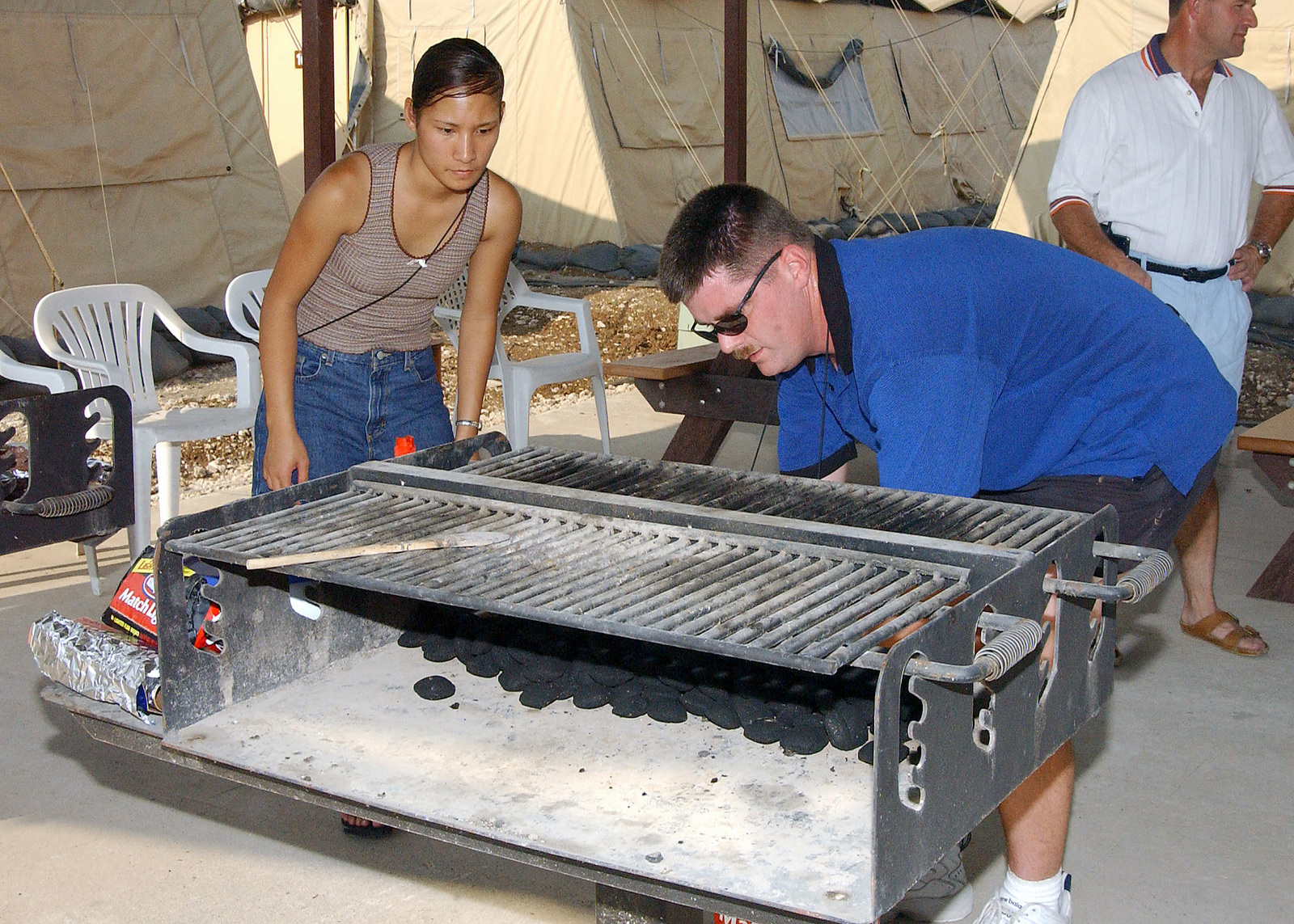 US Air Force (USAF) SENIOR AIRMAN (SRA) Marlena Cabrera-Smith and Technical Sergeant (TSGT) Buck Connor of the 10th Expeditionary Medical Squadron (EMS) stoke a grill in preparation for their deployed Birthday Party, at Incirlik Air Base (AB), Turkey, in support of Operation NORTHERN WATCH