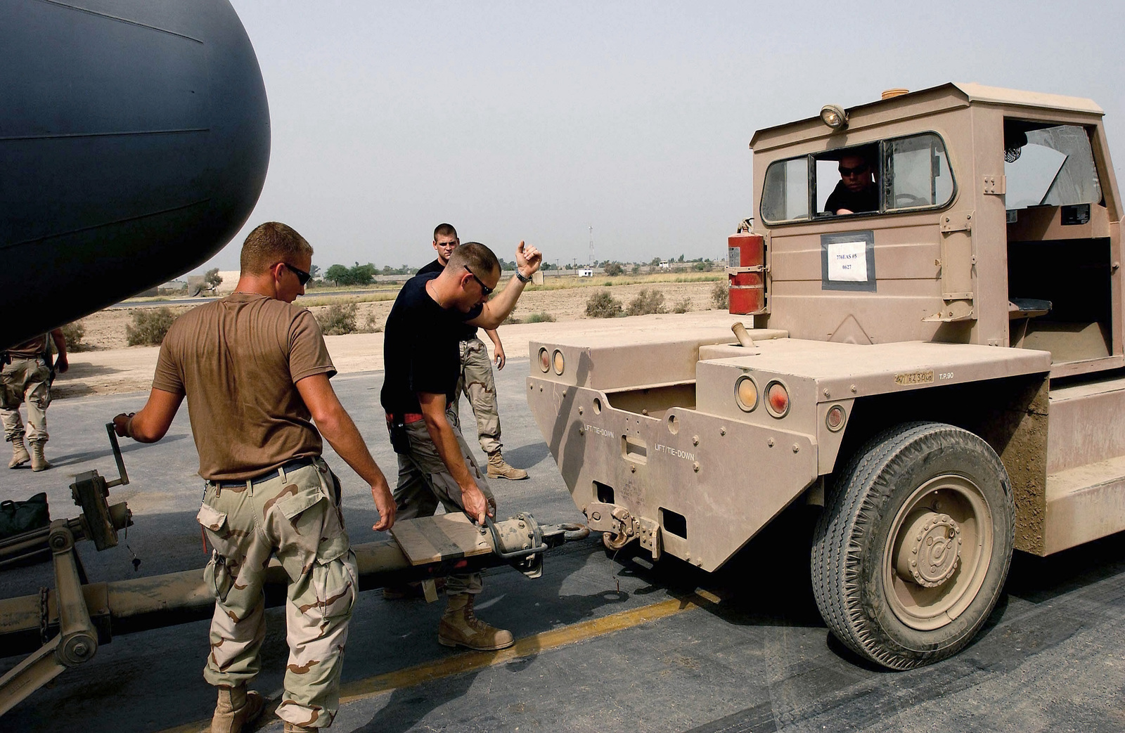 US Air Force (USAF) AIRMAN First Class (A1C) Derek Smith, an engine mechanic with the 776th Expeditionary Airlift Squadron (EAS), connects a C-130 Hercules cargo aircraft to a aircraft Tug truck at a forward deployed location (FDL) in support of Operation ENDURING FREEDOM