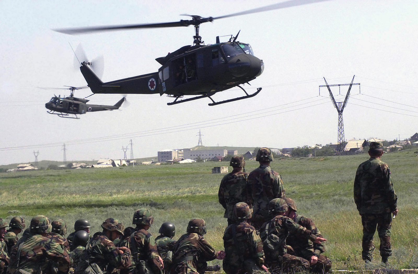 """Members of the Georgian Armed Forces sit and watch as Georgian UH-1H """"Huey"""" helicopters, lift off on an air mobile operational training flight, directed by US Air Force (USAF) personnel with the 6th Special Operations Squadron (SOS), out of Hurlburt Field, Florida, in support of the Georgia Train and Equip Program"""
