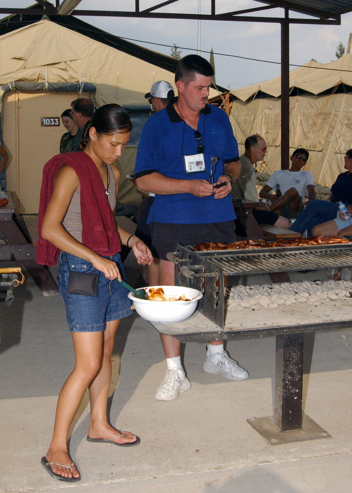 US Air Force (USAF) SENIOR AIRMAN (SRA) Marlena Cabrera-Smith and Technical Sergeant (TSGT) Buck Connor toss ribs on the grill for the 10th Expeditionary Medical Squadron (EMS) Deployment Birthday Party, at a Tent City, on Incirlik Air Base (AB), Turkey, during Operation NORTHERN WATCH