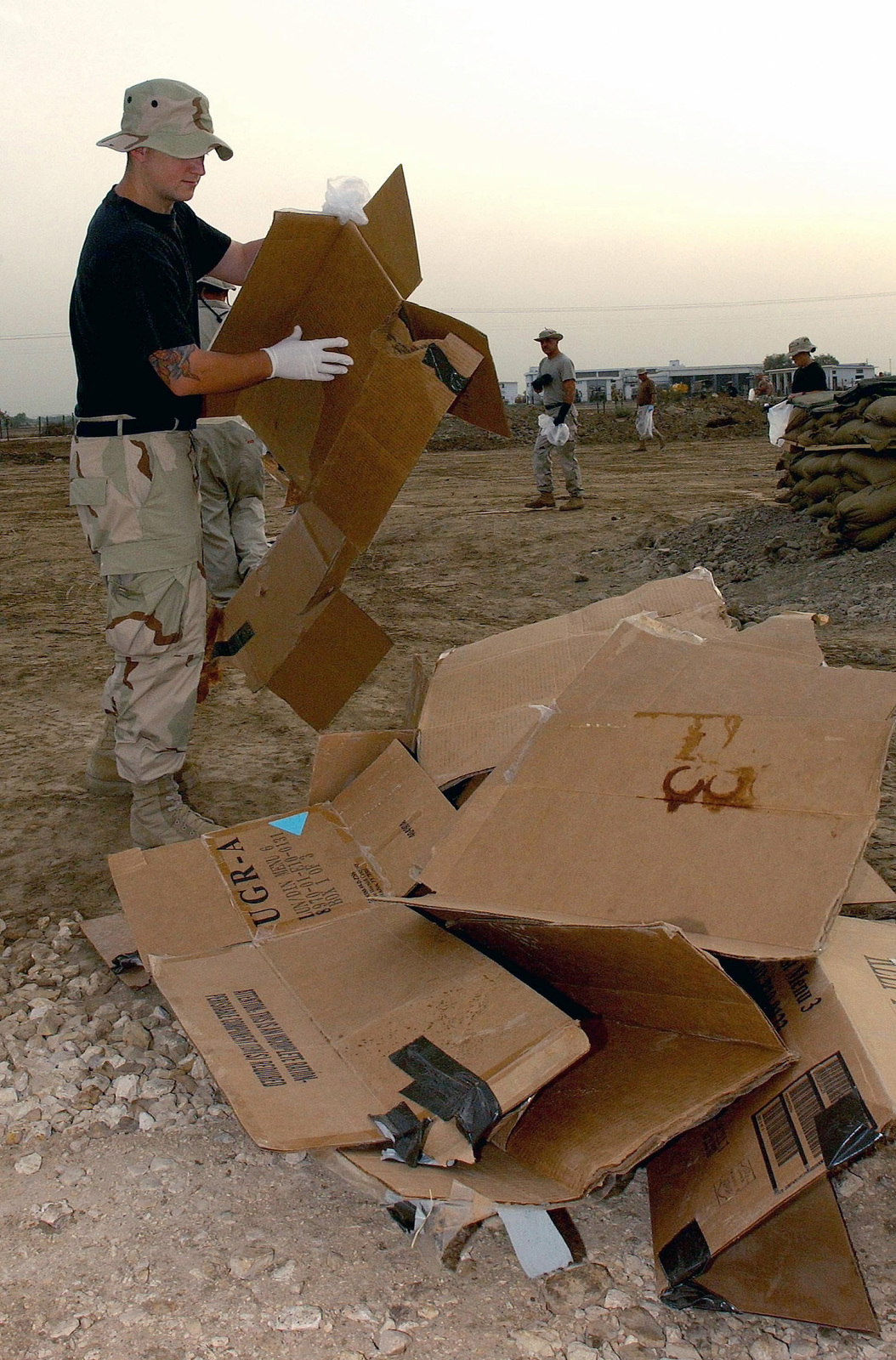 US Air Force (USAF) SENIOR AIRMAN (SRA) Bryan Stever, from the 11th Expeditionary Reconnaissance Squadron (ERS), piles cardboard debris into a centralized location during Operation Freedom Sweep at a forward deployed location (FDL) in support of Operation ENDURING FREEDOM