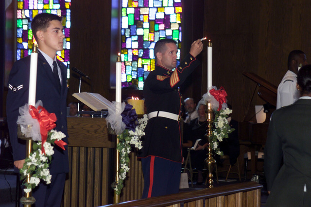 A US Marine Corps (USMC) GUNNERY Sergeant (GYSGT), lights a candle during a Memorial Service honoring the fallen of the September 11, 2001 attacks. The service was held at the Main Post Chapel, Joint Readiness Training Center, Fort Polk, Louisiana and included other US Military Service Members who participated in the candle lighting Service