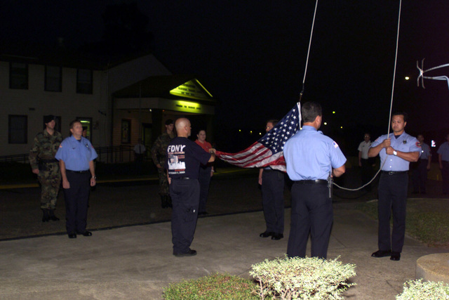 Firemen, paramedics and Military Police (MP) gathered outside the headquarters building at the Joint Readiness Training Center (JRTC), Fort Polk, LA, to participate in a flag raising ceremony honoring the one-year anniversary of the September 11th attacks