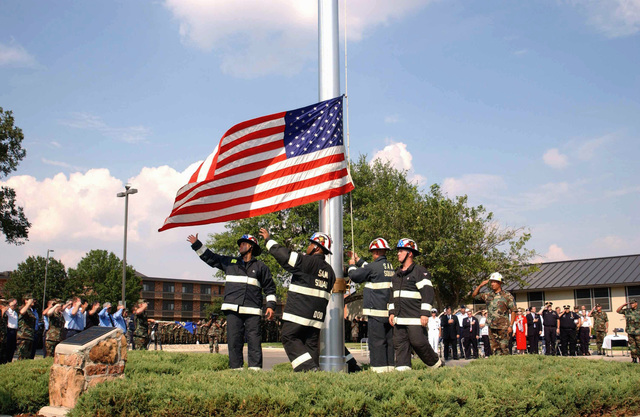 Members of the Soldiers, Sailors, Airmen, and Marines (SAM) Squad, multi-service, International Firefighter Combat Challenge Team, raise the American Flag, during a 9/11 Retreat Ceremony held in front of Wing Headquarters at Goodfellow Air Force Base (AFB), Texas (TX). Pictured left-to-right, US Air Force (USAF) STAFF Sergeant (SSGT) Alex Tamayo, US Army (USA) Sergeant (SGT) Omar Moore, US Navy (USN) PETTY Officer Third Class (PO3) Eric Tomczark, and US Marine Corps (USMC) SGT Joe Foucha