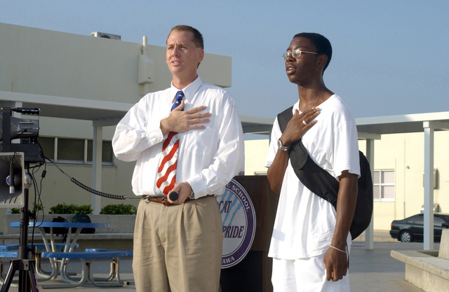 Mr. Jeff Arrington, Assistant Principal, Lester Middle School, and Tony Price, 8th grade Student and President of the National Junior Honors Society, lead the Pledge of Allegiance during a ceremony to commemorate the one year anniversary of the September 11th attacks, held at Camp Lester, Okinawa, Japan