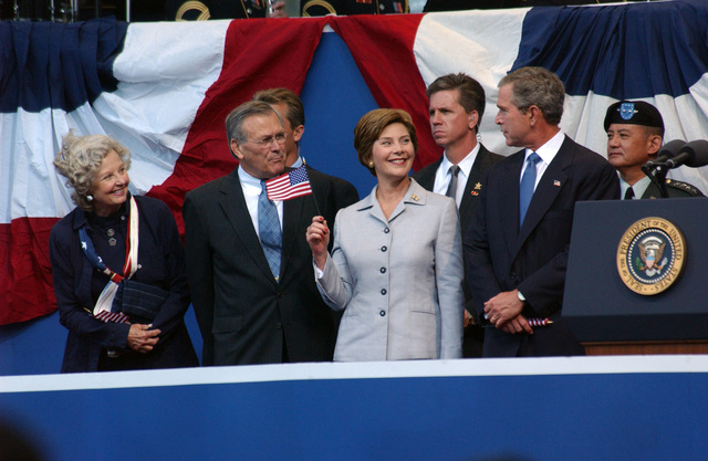 Mrs. Laura Bush (second, front right), First Lady of the United States, waves a small U.S. National Flag (ENSIGN), as the Honorable George W. Bush (front, right), President of the United States, The Honorable Donald H. Rumsfeld (second, front left), U.S. Secretary of Defense, and Mrs. Joyce Rumsfeld (front left), look on, at the conclusion of the September 11 (9/11) Memorial Service at the Pentagon on Sept. 11, 2002. This service marks the first anniversary of terrorists flying a commercial airliner into the Pentagon. (DoD photo by CHIEF PETTY Officer Johnny Bivera) (Released)