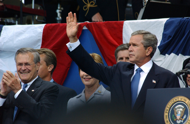 The Honorable Donald H. Rumsfeld (left), U.S. Secretary of Defense, applauds as the Honorable George W. Bush (right, waving), President of the United States, and Mrs. Laura Bush (center), First Lady of the United States, arrive at the Pentagon on Sept. 11, 2002, to participate in the September 11 (9/11) Memorial Service. This service marks the first anniversary of terrorists flying a commercial airliner into the Pentagon. (DoD photo by CHIEF PETTY Officer Johnny Bivera) (Released)