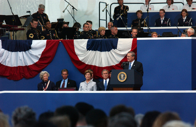 The Honorable George W. Bush (seated, right), President of the United States, Mrs. Laura Bush (seated, center right), First Lady of the United States, and Mrs. Joyce Rumsfeld (seated, left) listen as The Honorable Donald H. Rumsfeld (at the lectern), U.S. Secretary of Defense, speaks during the September 11 (9/11) Memorial Service at the Pentagon on Sept. 11, 2002. This service marks the first anniversary of terrorists flying a commercial airliner into the Pentagon. (DoD photo by CHIEF PETTY Officer Johnny Bivera) (Released)