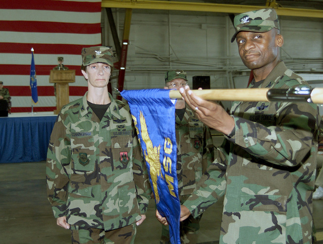 US Air Force (USAF) Colonel (COL) Joan M. Cunningham (left) In-coming Commander, 375th Mission Support Group (MSG), is presented with the Units Guidon by USAF COL Darren W. McDew (foreground) during a Change of Command Ceremony, conducted at Scott Air Force Base (AFB), Illinois (IL)