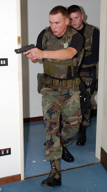 His M9 9mm Beretta Pistol drawn, US Air Force (USAF) AIRMAN (AMN) Jarrod Getz, enters a room as AIRMAN First Class (A1C) Casey Snyder, follows closely behind, both are assigned to the 31st Security Forces Squadron (SFS), at Aviano Air Base (AB), Italy, during their realistic breach training