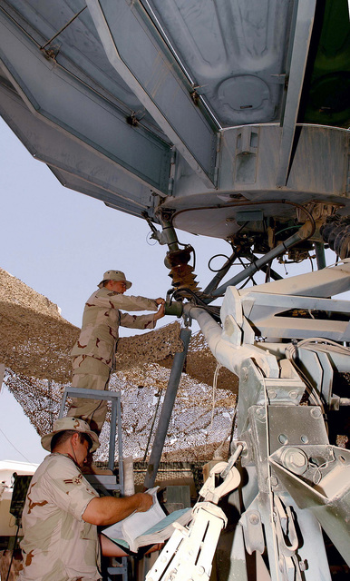 STAFF Sergeant (SSGT) Brian Cooney and AIRMAN First Class (A1C) Josue Rivera, left, both from the 438th Expeditionary Communications Flight, perform an alignment of the elevation data package on a quick reaction satellite antenna at a forward deployed location (FDL), in support of Operation ENDURING FREEDOM