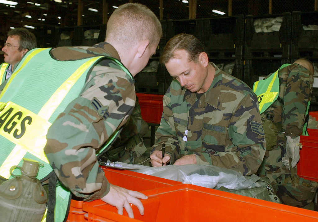 US Air Force (USAF) AIRMAN First Class (A1C) Caleb Crass, assigned to the 52nd Logistics Readiness Squadron (LRS), assists with out-processing procedures and matching stock numbers to various chemical gear issued to STAFF Sergeant (SSGT) Scott M. Maier, 52nd Operations Support Squadron (OSS)