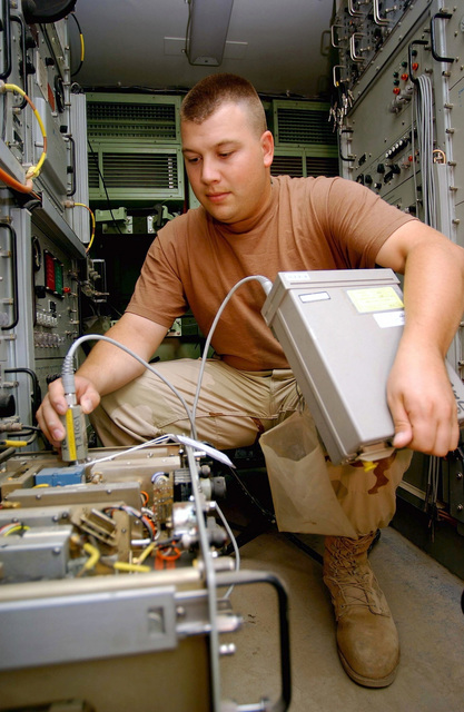 US Air Force (USAF) STAFF Sergeant (SSGT) Brian Cooney, a satellite and wide-band communications specialist from the 438th Expeditionary Communications Flight, performs a preventative maintenance inspection on a frequency converter in support of Operation ENDURING FREEDOM