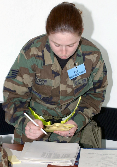 US Air Force (USAF) STAFF Sergeant (SSGT) Michelle Wilkerson, 52nd Medical Operations Squadron (MOS), counts and reviews shot records needed for processing at the Personnel Processing Center on September 18th, 2002
