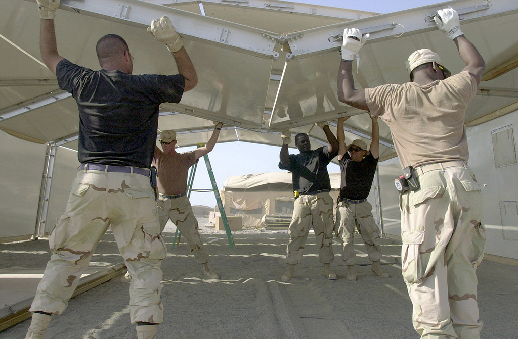 A team of US Air Force (USAF) civil engineers from the 321st Expeditionary Support Squadron (ESS) work together to guide a general purpose shelter panel into place for a Base Exchange facility at a forward-deployed location (FDL) in the Arabian Gulf region