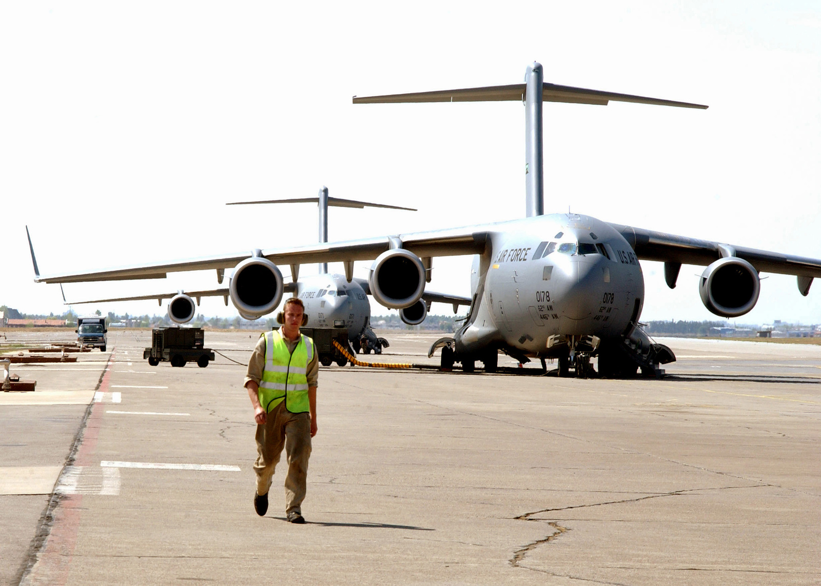 Against the backdrop of two US Air Force (USAF) C-17 cargo aircraft a Royal Air Force (RAF) flight technician walks on the flight line, in supporting Operation NORTHERN WATCH at Incirlik Air Base (AB), Turkey