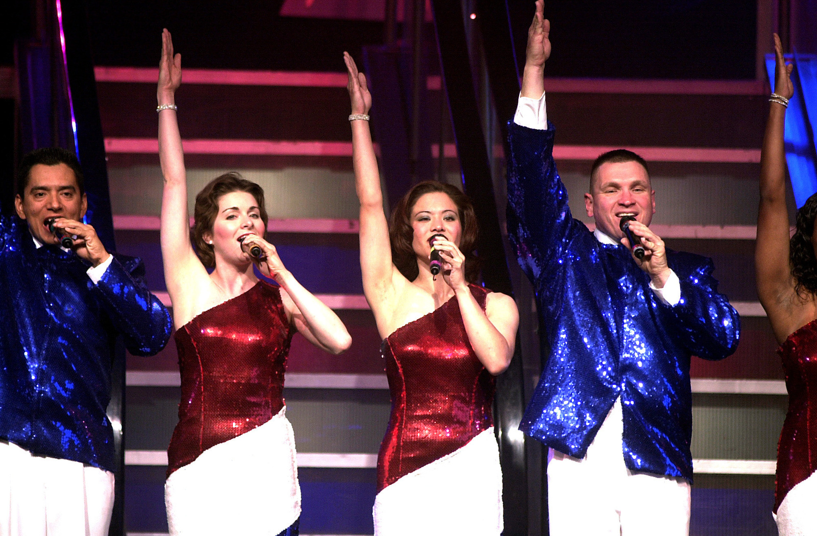 """From the left, US Air Force (USAF) Technical Sergeant (TSGT) Max Hernandez, Jr., Captain (CAPT) Susan Neidlinger, AIRMAN First Class (A1C) Angie Long, and MASTER Sergeant (MSGT) Bryan Langerud, perform the opening number """"American, I Still Can Hear Your Song"""" during a """"Tops In Blue"""" concert at Ramstein Air Base (AB), Germany"""