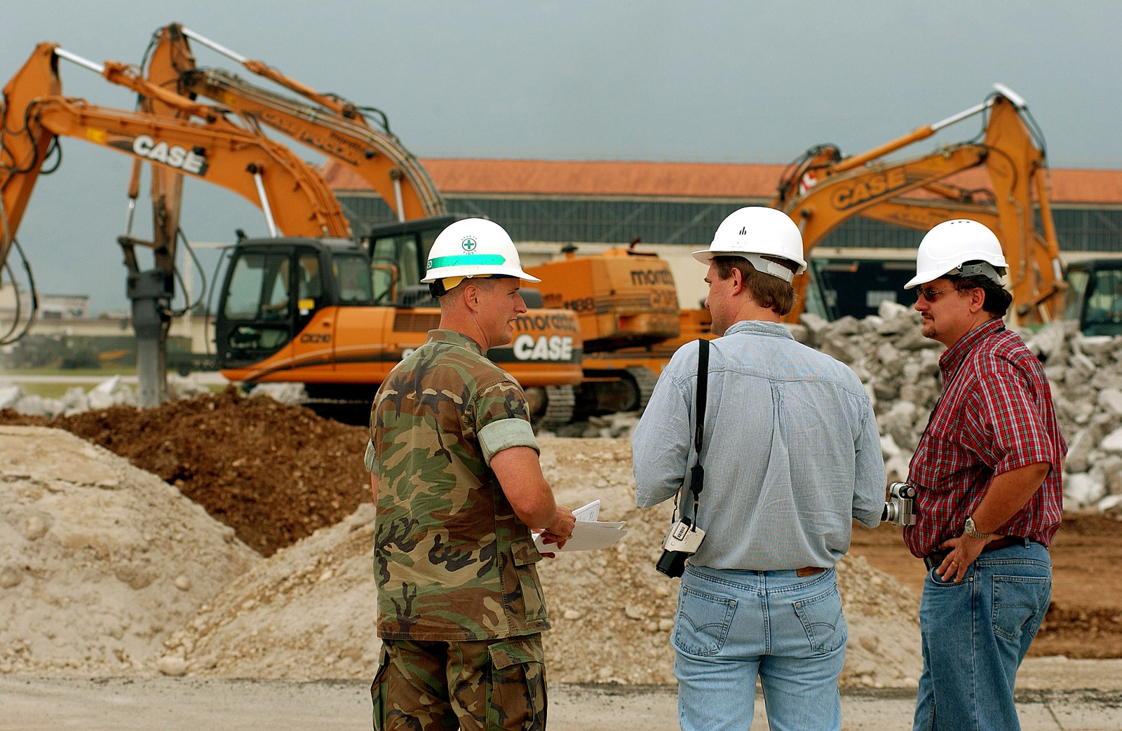 US Air Force (USAF) Lieutenant Commander (LCDR) Scot Sanders, left, Resident Officer in Charge of Construction, Kent Harris, center, a reporter with Stars and Stripes along with Aleksander Andrzejewski, from the 16th Air Force Plans Management Office (PMO), discuss a paving project at Aviano Air Base (AB), Italy