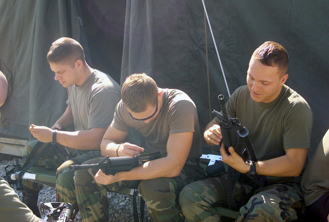 United States Marine Corps (USMC) Corporal (CPL) Joseph Richardson, left, CPL Jarred Goff, center and Sergeant (SGT) Eric Buell from the 24th Marine Expeditionary Unit (MEU) Radio Battalion, clean weapons at Camp Able Sentry, in Macedonia, the Former Republic of Yugoslavia