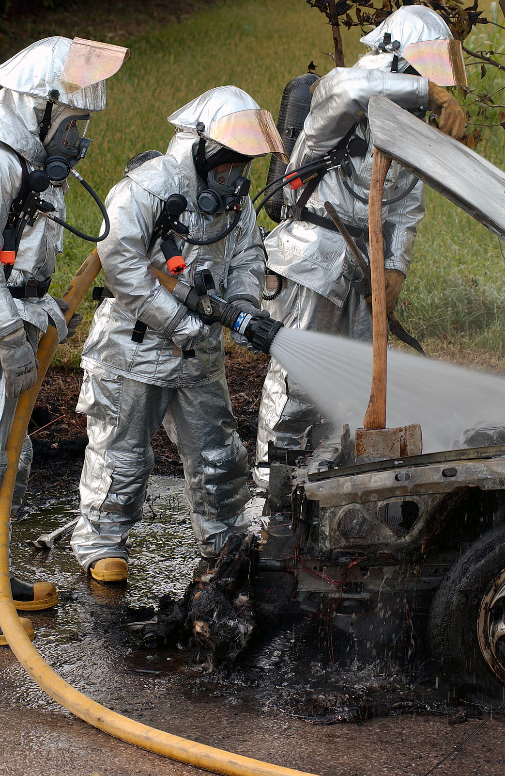 US Air Force (USAF) personnel assigned to the 31st Civil Engineer Squadron (CES), Fire Department, dressed in full proximity suits spray water on the personal vehicle belonging to US Air Force (USAF) AIRMAN First Class (A1C) Khalio Borum at Aviano Air Base (AB), Italy. The vehicle caught fire after experiencing mechanical difficulties