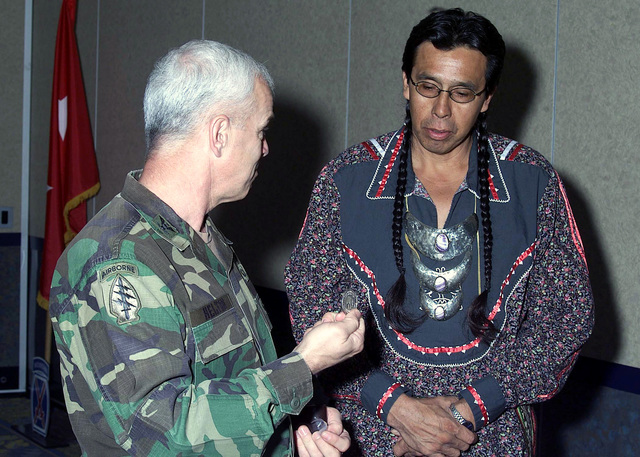 Colonel (COL) Emory R. Helton, Ft. Drum Garrison Commander, explains the rich tradition and history of 'Coins' in the Army to Tododaho CHIEF Sidney Hill (an Onondaga Indian), Spiritual leader of the six-nation Haudenosaunee (Iroquois) group