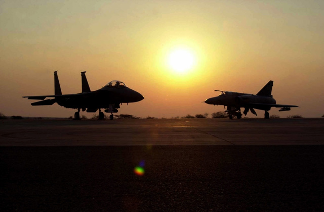 A US Air Force (USAF) F-15C Eagle aircraft (left) and a South African Air Force (SAAF) Cheetah C Multi-role Fighter aircraft, parked on the flight line at Louis Trichardt Air Force Base (AFB), South Africa. USAF personnel are deployed at Louis Trichardt AFB in preparation for the first ever live-fire bilateral aircraft exercise with the South African Air Force (SAAF). The setting sun silhouettes the image