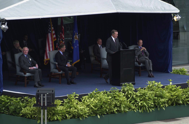 Former US President George Herbert Walker Bush, speaks during the Rededication Ceremony for the American Air Museum at Royal Air Force (RAF) Duxford, Cambridgeshire, United Kingdom (UK). Seated to the right of Mr. Bush is His Royal Highness, Charles, Prince of Wales and seated to the far left is His Royal Highness, Edward, Duke of Kent