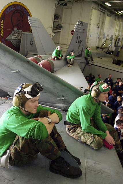 US Navy (USN) crewmembers from Electronic Attack Squadron (VAQ-139), Cougars, Naval Air Station (NAS) Whidbey Island, Washington (WA), Aviation Structural Mechanic AIRMAN (AMAN) Scott Wood and Aviation Structural Mechanic Third Class (AM3) Richard Hakes, sit on the wing of a USN EA-6B Prowler aircraft to listen to USN MASTER CHIEF PETTY Officer of the Navy (MCPON) Terry D. Scott [not shown] during his visit on board the Nimitz Class Aircraft Carrier USS ABRAHAM LINCOLN (CVN 72)