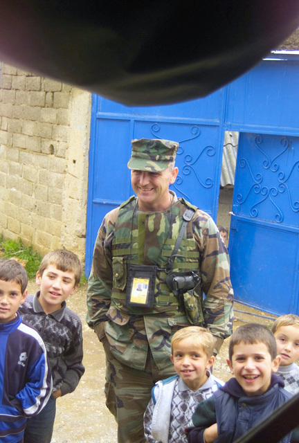 Armed with a Beretta sidearm, United States Marine Corps (USMC) STAFF Sergeant (SSG) James Eddleman, Marine Liaison Element (MLE), assigned to the 24th Marine Expeditionary Unit (MEU) enjoys the company of some local children, during Operation DYNAMIC RESPONSE 2002, in Kosovo