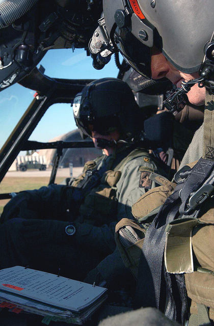 US Army (USA) CHIEF Warrant Officer (CWO) Rick Cote, (Pilot), and USA Major (MAJ) Chris Speer (Co-Pilot), both assigned to Bravo/Company, 5/158th Aviation Regiment, review the preflight check list, inside the cockpit of their UH-60 Black Hawk helicopter, on the flight line at Aviano Air Base (AB), Italy, in preparation for a Joint Training Exercise with the Polish Armed Forces called Exercise VICTORY STRIKE III