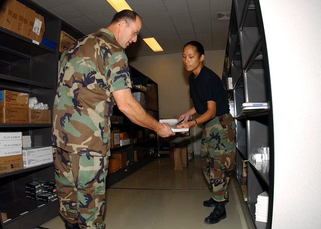 US Air Force (USAF) Lieutenant Colonel (LTC) Jerry Limoge (left), Commander, 10th Expeditionary Medical Squadron (EMS) receives supplies from USAF SENIOR AIRMAN (SRA) Marlena Cabrera-Smith, Medical Supply Technician, 39th Medical Group (MDG), 10th EMS, inside the medical supply warehouse, while deployed at Incirlik Air Base (AB), Turkey, in support of Combined Task Force (CTF), Operation NORTHERN WATCH