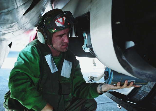 US Navy (USN) Photographer's Mate AIRMAN (PHAN) Steven Neel, Strike Fighter Squadron 31 (VF-31), Naval Air Station (NAS) Oceana, Virginia (VA), removes a 153 film canister from a Tactical Airborne Reconnaissance Pod System (TARPS) Pod, attached to a USN F-14D Tomcat fighter aboard the Nimitz Class Aircraft Carrier USS ABRAHAM LINCOLN (CVN 72). The LINCOLN and Carrier Air Wing 14 (CVW-14) are conducting combat operations in support of Operation ENDURING FREEDOM