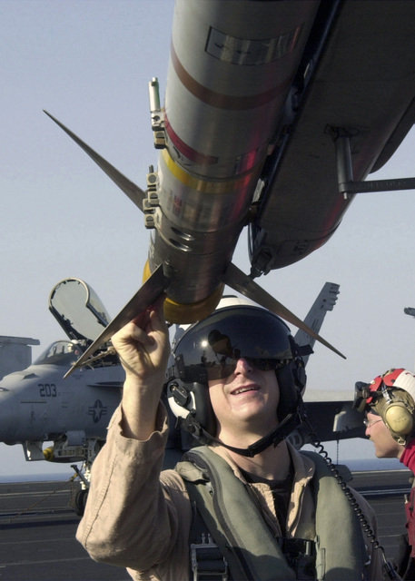 US Navy (USN) Lieutenant Commander (LCDR) John Howland, Strike Fighter Squadron 113 (VFA-113), Naval Air Station (NAS) Lemoore, California (CA), checks a Sidewinder (AIM-7F) missile during preflight checks to ensure it is hung correctly on his USN F/A-18C Hornet fighter on board the USN Nimitz Class Aircraft Carrier USS ABRAHAM LINCOLN (CVN 72). The LINCOLN and Carrier Air Wing 14 (CVW-14) are conducting combat operations in support of Operation ENDURING FREEDOM