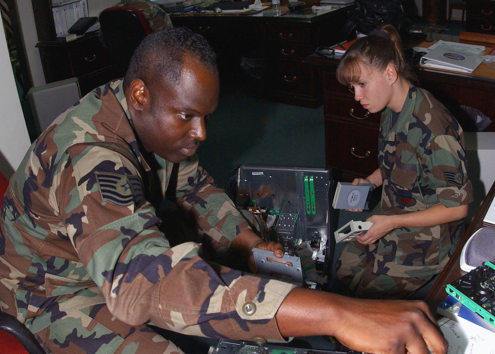 US Air Force (USAF) MASTER Sergeant (MSGT) Greg Van Buren (left) and USAF STAFF Sergeant (SSGT) Cathe Rynkowski, combine their expertise, while installing new computers for the Combined Task Force (CTF) Headquarters, at Incirlik Air Base (AB), Turkey, while deployed in support of Operation NORTHERN WATCH