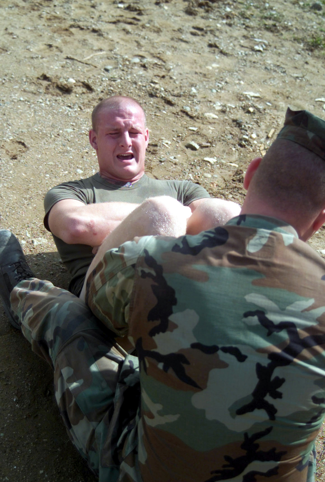 US Marine Corps (USMC) Sergeant (SGT) Alex Vanbreukelen, S-4 Supply, 24th Marine Expeditionary Unit (MEU), strains to complete the sit up portion of a Physical Fitness Test, while SGT Neal E. Stillman, holds his feet, aboard Camp Casablanca, in Kosovo, during Operation DYNAMIC RESPONSE 2002