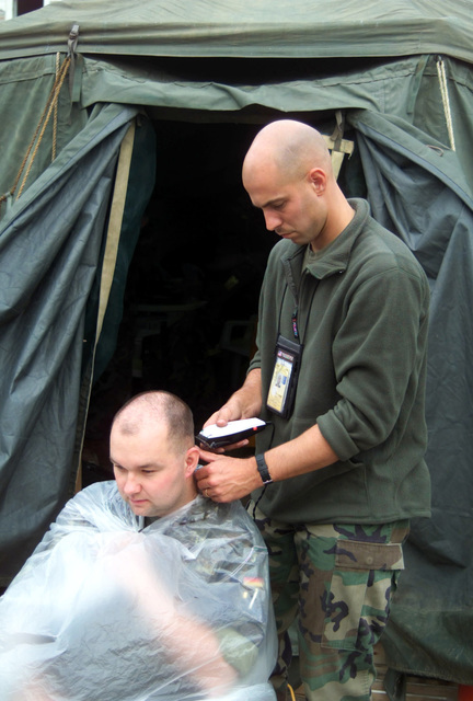 US Marine Corps (USMC) STAFF Sergeant (SSGT) John S. Blackford, Radio Battalion 24th Marine Expeditionary Unit (MEU), Cuts the hair of a Federal Republic of Germany (FRG) Soldier, Captain (CAPT) Thomas Ruehe, at the Blue Residence in Prizren, Kosovo, during Operation DYNAMIC RESPONSE 2002