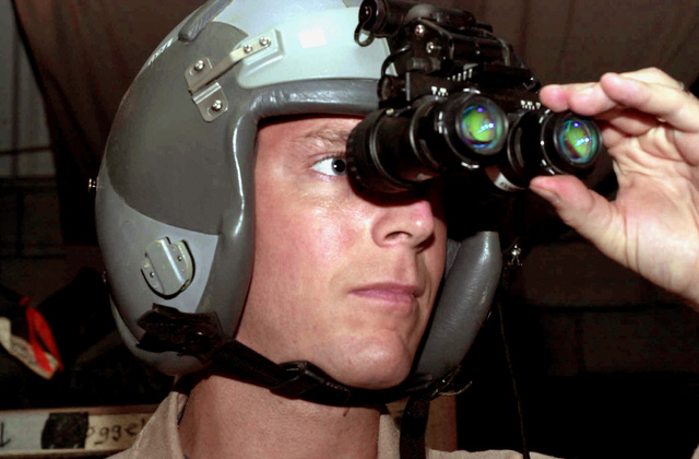 US Air Force (USAF) Captain (CPT) Karl Boehle, Life Support Section CHIEF, 777th Expeditionary Airlift Squadron (EAS), ensures that night vision goggles are functional, before issuing them aircrews, while forwardly deployed in support of Operation ENDURING FREEDOM