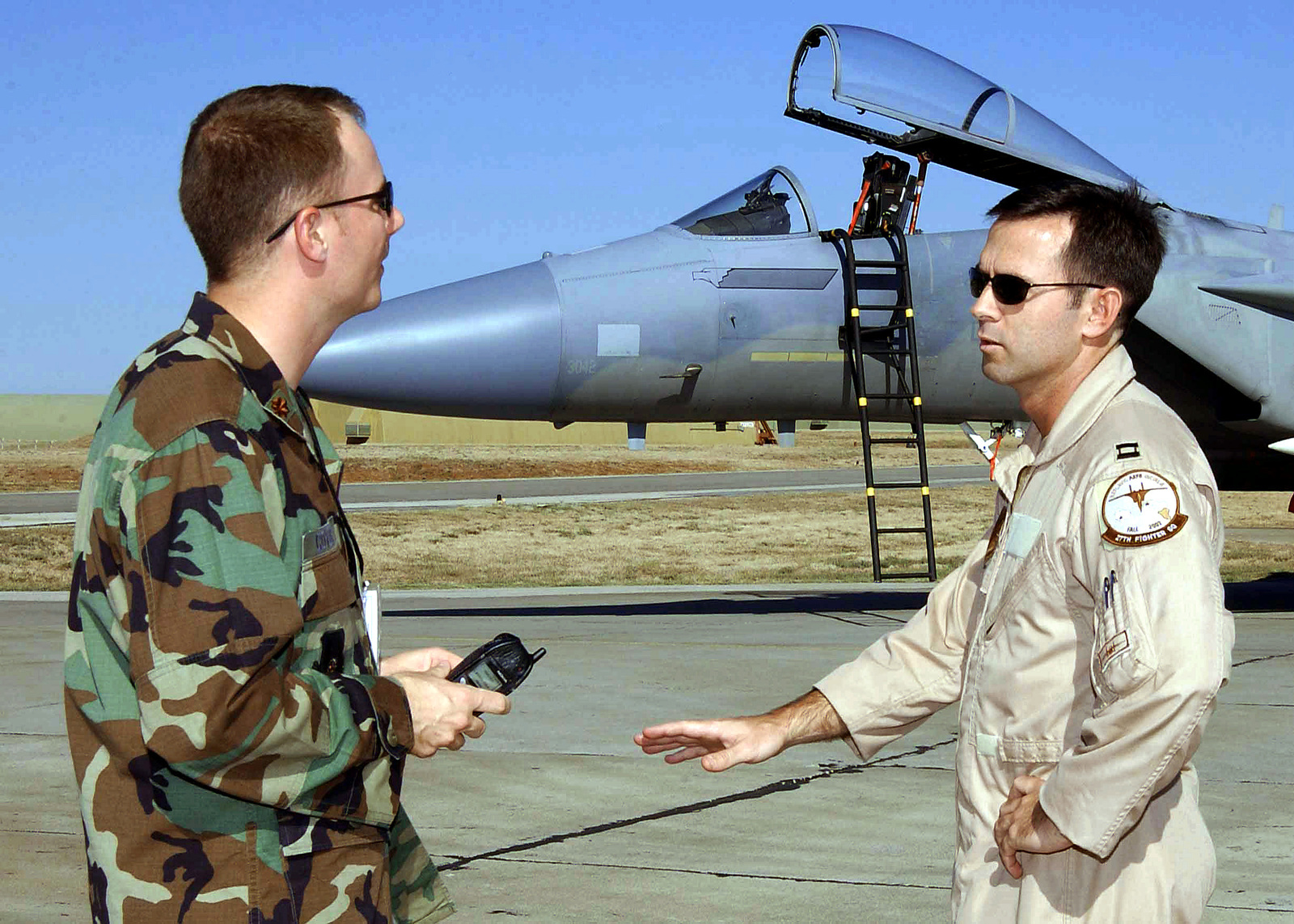 US Air Force (USAF) Major (MAJ) Scott Covode (left), Public Affairs Officer (PAO), talks with USAF Captain (CPT) Patrick Driscoll, F-15C Eagle aircraft Pilot assigned to the 25th Expeditionary Fighter Squadron (EFS), about CPT Driscoll upcoming interview Cable News Network (CNN), on the flight line at Incirlik Air Base (AB), Turkey, while deployed support of Combined Task Force (CTF), Operation NORTHERN WATCH