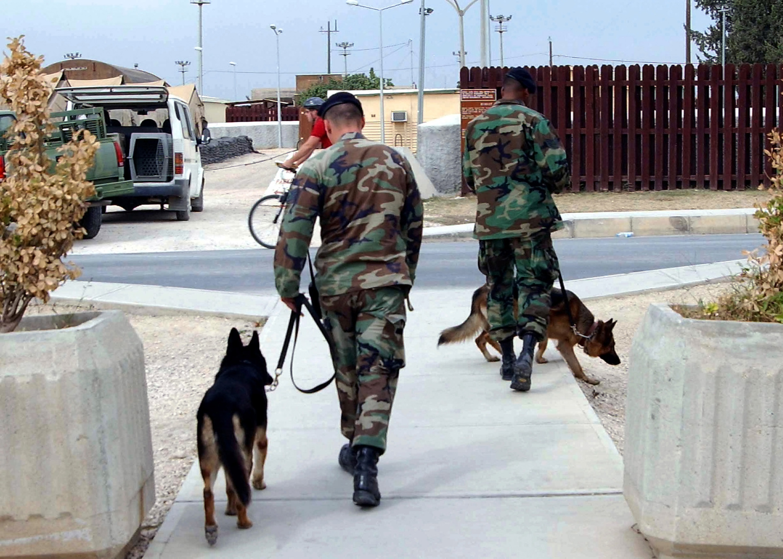 US Air Force (USAF) STAFF Sergeant (SSGT) Len Arsenault (foreground) and USAF SSGT Hewitt Cox, both Military Working Dog Handlers, 39th Security Forces Squadron (SFS), leave with their dogs Borsky and Tarra, after conducting a routine search for explosives, inside the morale tent at Incirlik Air Base (AB), Turkey, while deployed in support of Operation NORTHERN WATCH