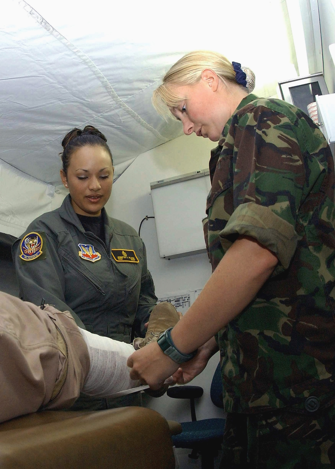 US Air Force (USAF) STAFF Sergeant (SSGT) Jennifer Hilker (left), Medical Technician, deployed with the 78th Expeditionary Fighter Squadron (EFS), and British (UK), Royal Air Force (RAF), Sergeant (SGT) Kelly Purdie, dresses a patient's leg wound inside the medical clinic in tent city at Incirlik Air Base, Turkey, while deployed in support of Combined Task Force, Operation NORTHERN WATCH